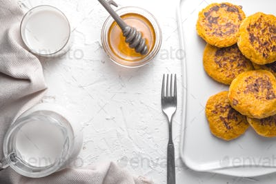 Honey, pumpkin pancakes, hemp milk on a white table frame