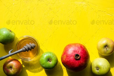 Apples with honey, pomegranate on a yellow table for the Jewish New Year