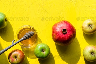 Apples with honey, pomegranate on a yellow table for the Jewish New Year closeup