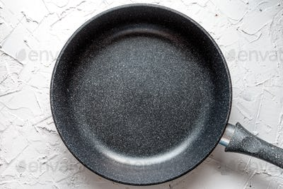 Aluminum frying pan with non-stick coating on white salt