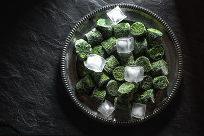 Frozen spinach in briquettes and ice on a plate in the center of the table