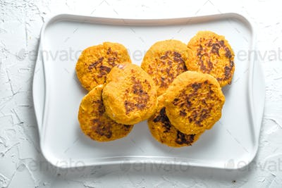 Vegetarian pumpkin pancakes on a white plate on a white background