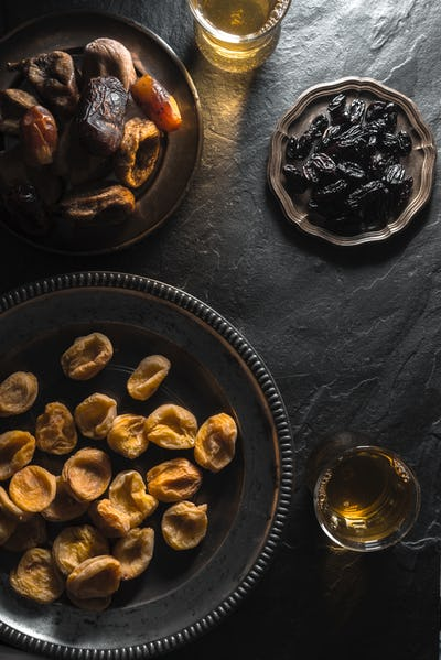 Tea-drinking in Oriental style with dates, dried apricots and raisins on a stone table