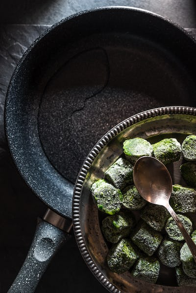 Frying pan and a plate of frozen spinach on slate