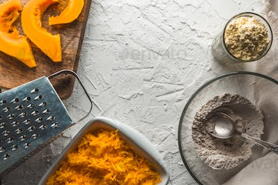Grater, grated pumpkin, flour on a white table for making pancakes