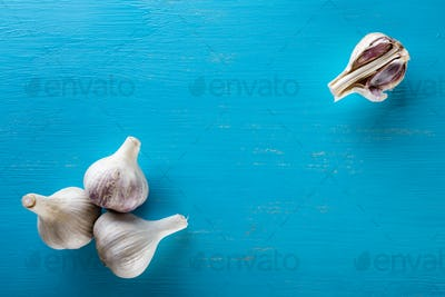 Three heads and cloves of the garlic on a wooden table