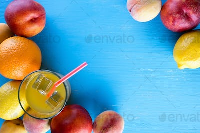Fresh juicy fruit and cold juice on blue wooden table