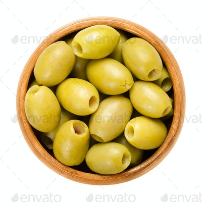 Pitted and marinated green olives in wooden bowl