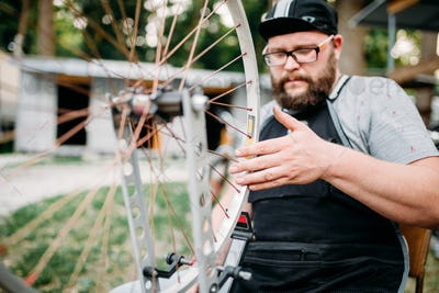Mechanic adjusts bike spokes and repair wheel