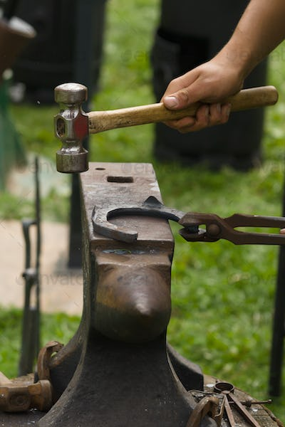 Farrier Making a Horsehoe on an Anvil