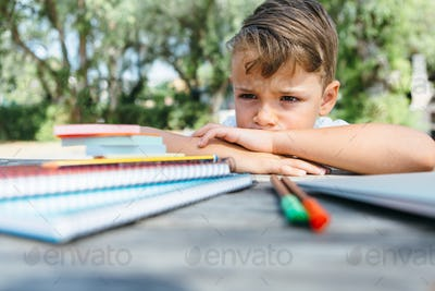 Little schoolboy with notepads at table