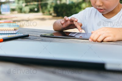Crop child studying with tablet