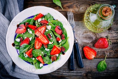 Spinach salad with strawberries, feta cheese, balsamic and pecan nuts