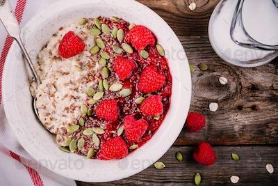 Healthy breakfast: oatmeal with fresh raspberries, flax seeds and pumpkin seeds