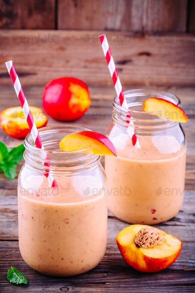 Peach smoothies in a mason jar with mint on wooden background