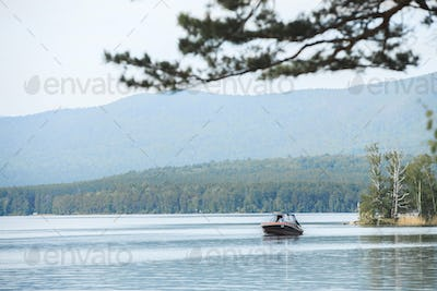 Motor boat floats on water of lake