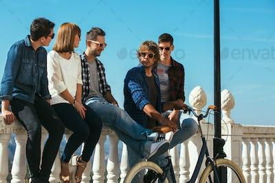 Young stylish friends sitting on balcony