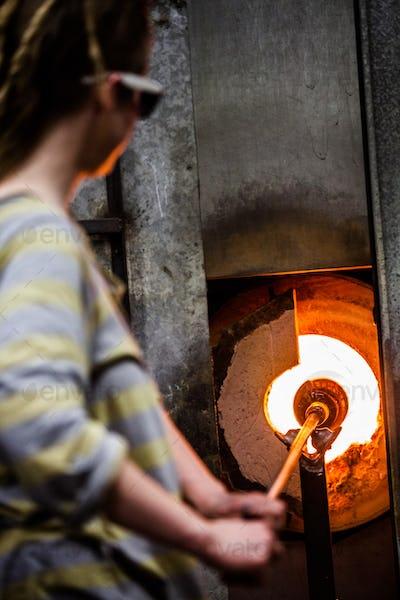 Glassmaker Flashing Piece of Glass in the Kiln