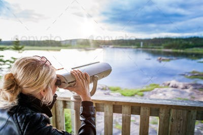 Young Woman Looking at the Amazing Nature Through a Binocular in