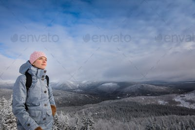 Young Woman Looking at the View from the Top of a Mountain in Wi
