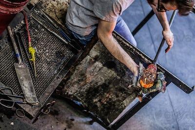 Man Hands Closeup Working on a Blown Glass Piece