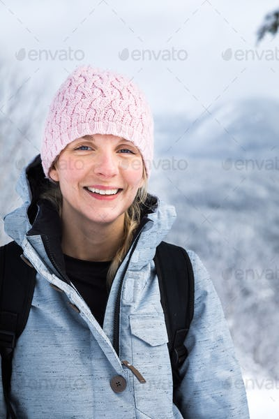 Happy Woman Portrait on the Top of a Mountain in Winter