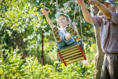 Senior man pushing cheerful grandson on swing