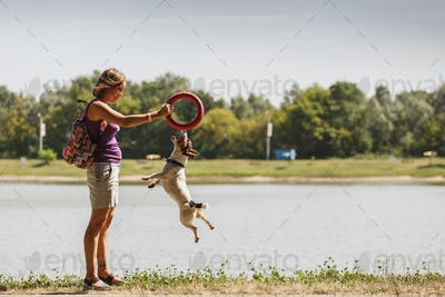 Woman playing with dog on nature