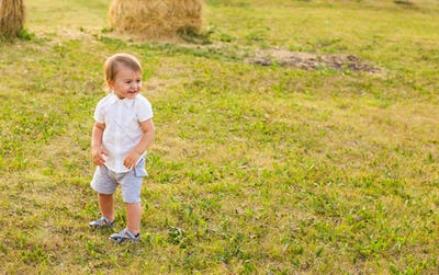 Happy laughing baby boy playing on summer or autumn nature.