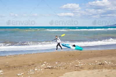 Young man carrying his kayak along the shore