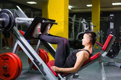 Active young woman doing exercise for legs on special equipment in gym.