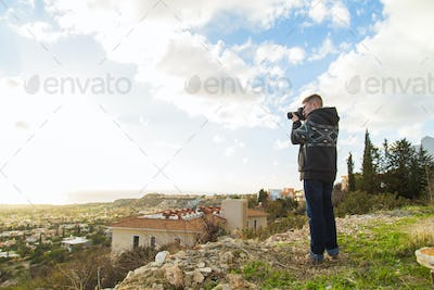 Traveler photographer with digital camera on top of the mountain.