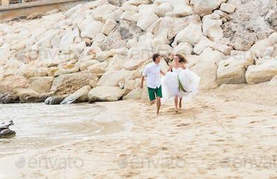 Happy just married young wedding couple celebrating and have fun at beautiful beach