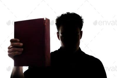 Man figure in silhouette showing a book