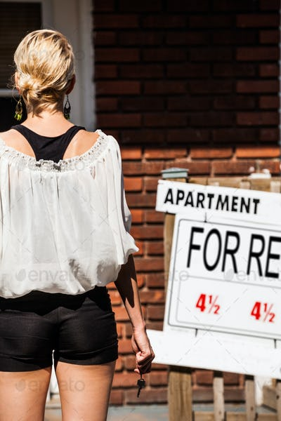 Young Woman standing in front of her new apartment