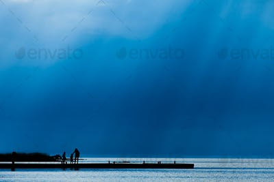 Dock in silhouette with people and rays of light