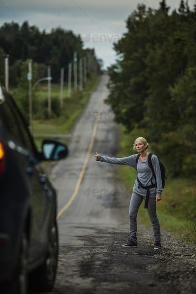 Blonde Woman Hitchhiking on the Side of the Road