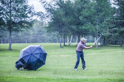 Golfer on a Rainy Day Swigning in the Fairway
