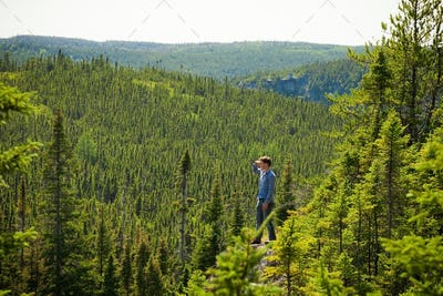 Young man on a rock in the middle of the nature