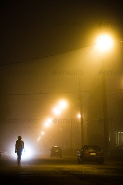 Woman alone in the foggy street