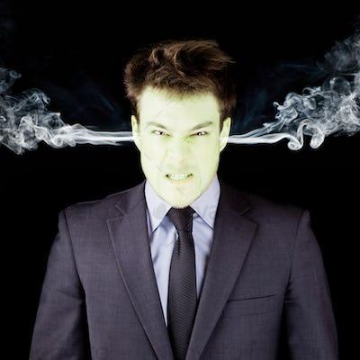 Furious businessman getting green face