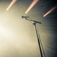 Microphone on empty stage waiting for a voice