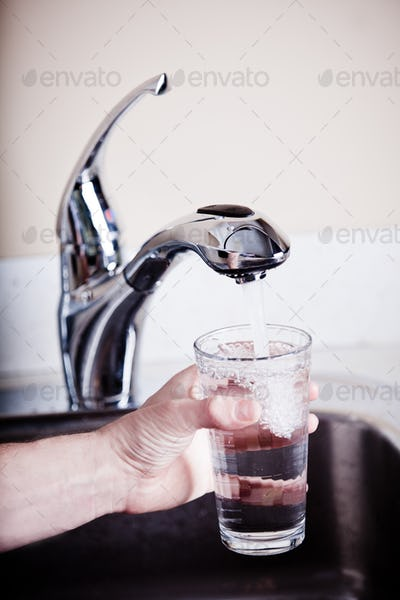 Thirsty man filling a big glass of water