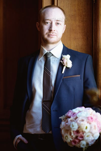 Handsome groom in suit in the hall