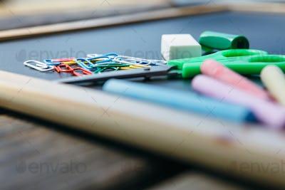 Office supplies and chalks on blackboard