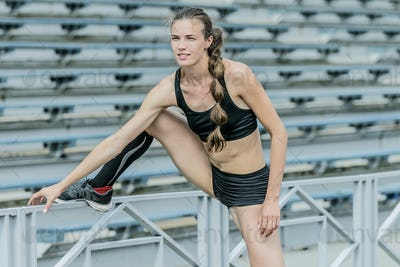 Young woman exercises in stadium
