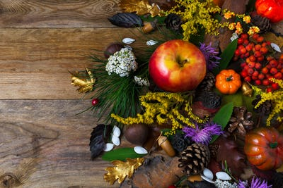 Fall decoration with flowers and apple on wooden table