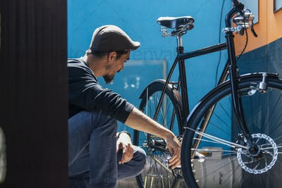 Side view of worker looking at his bike