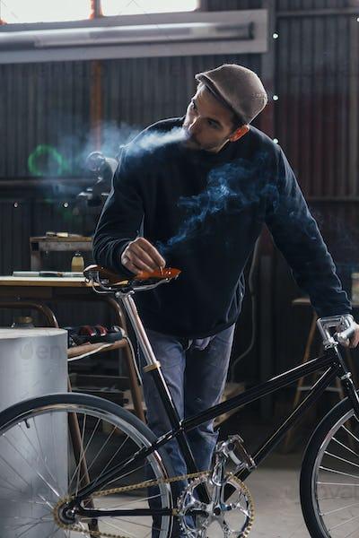 Smoking constructor looking away near bike