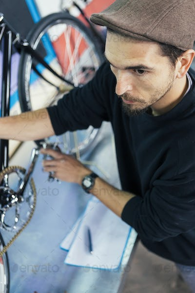 Serious bearded man holding bicycle